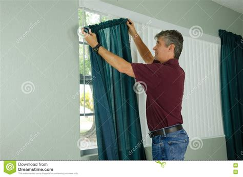 what kind of man curtains man hanging curtains home repair maintenance stock photo