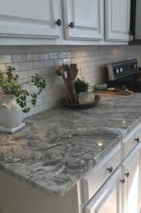 brown granite with small white subway tiles and warm gray grout our home