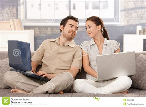 couple on sofa young couple sitting on sofa using laptop smiling royalty