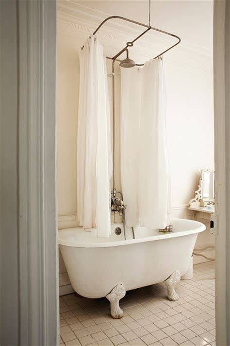 clawfoot tub with a curtain and decor