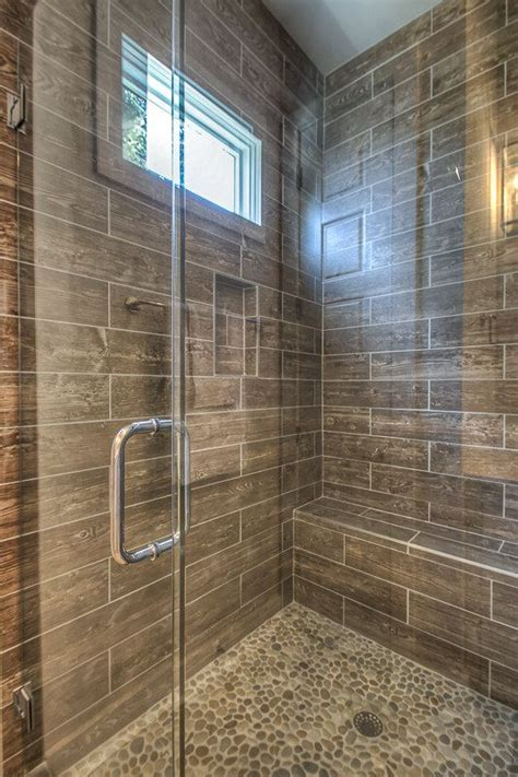 Faux wood plank shower wall tile and pebble shower floor