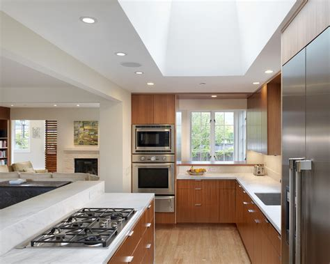 modern interior open kitchens designs with recessed interior stove on white granite countertop with wood