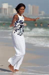 Michelle obama in blotchy top and white pants on panama beach
