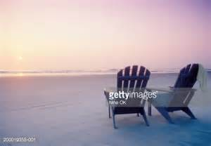 Two adirondack style chairs on beach facing ocean sunrise stock photo