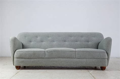 curved three seat sofa with light blue fabric upholstery