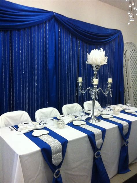 curtains for wedding reception head table with royal blue back drop and crystal step