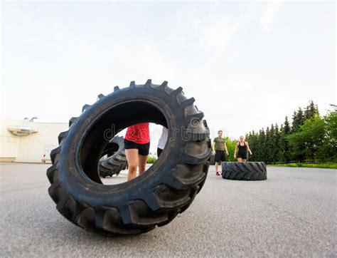 athletes motivating friend  flipping tire stock image image  personal equipment