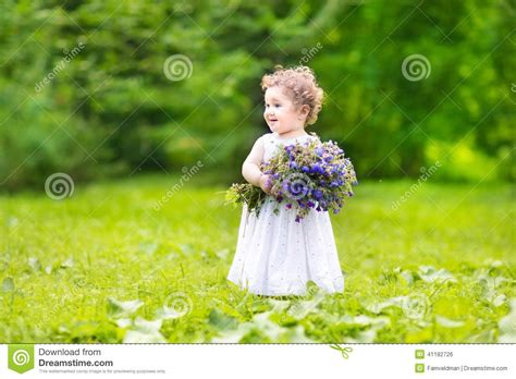 beautiful baby photos with flowers beautiful baby carrying flowers in a garden stock