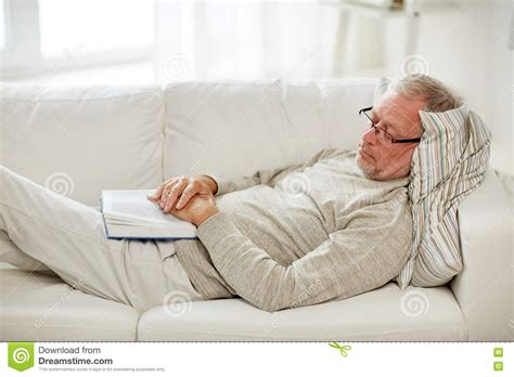 i sleep on a couch senior man sleeping on sofa with book at home stock image