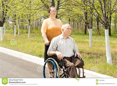 one leg wheelchair being taken for a walk in a wheelchair stock photo