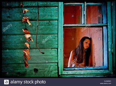 buying a house with a girlfriend sad beautiful girl with long black hair in the window of an old house stock photo