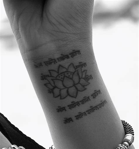 wrist tattoo font sanskrit lettering and lotus on right wrist