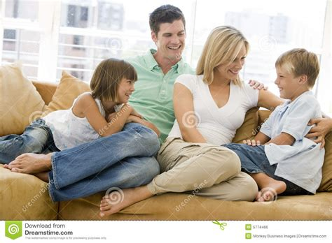 family sitting in living room smiling stock photo image