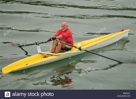 single scull boat a healthy fit middle aged man sculling alone in a single