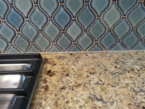 close up new venetian gold granite countertop with blue arabesque tiles backsplash bthrm
