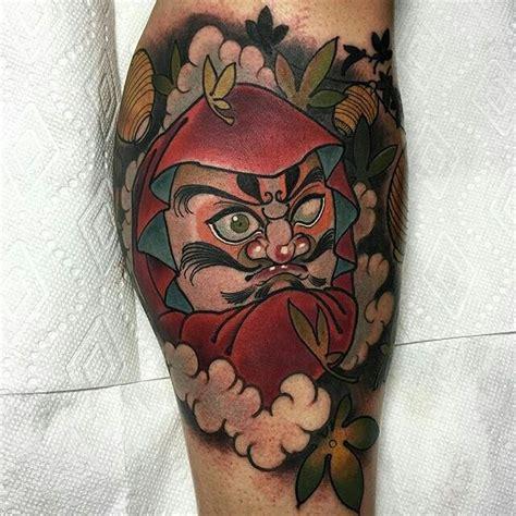 simple neo traditional tattoo illustrative style colored leg tattoo of big daruma doll