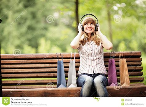 sitting on a park bench song listening to in headphones royalty free