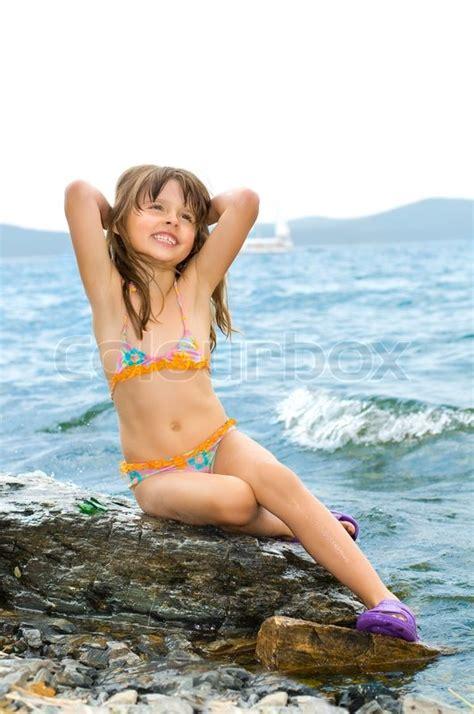 Pleasure Beautiful Little Girl Sit On Calculus On Coast In Stock Photo Colourbox
