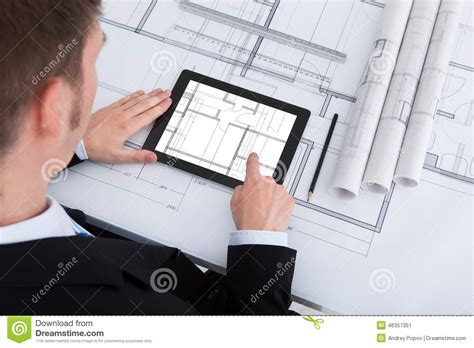 male architect with digital tablet studying plans in architect using digital tablet on blueprint in office