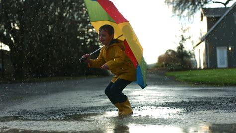Boots Anak Anti Hujan Karakter 1 boy jumping in puddles with umbrella motion