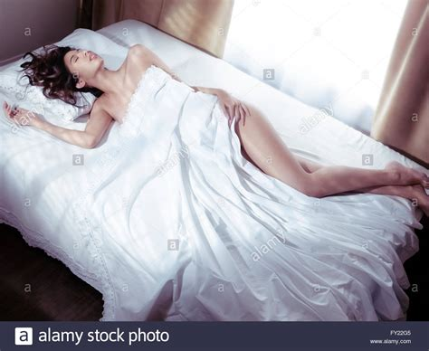 woman sleeping in bed young woman sleeping in bed covered with white sheets