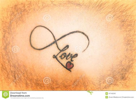 abstract tattoo on skin that says love with smal red heart