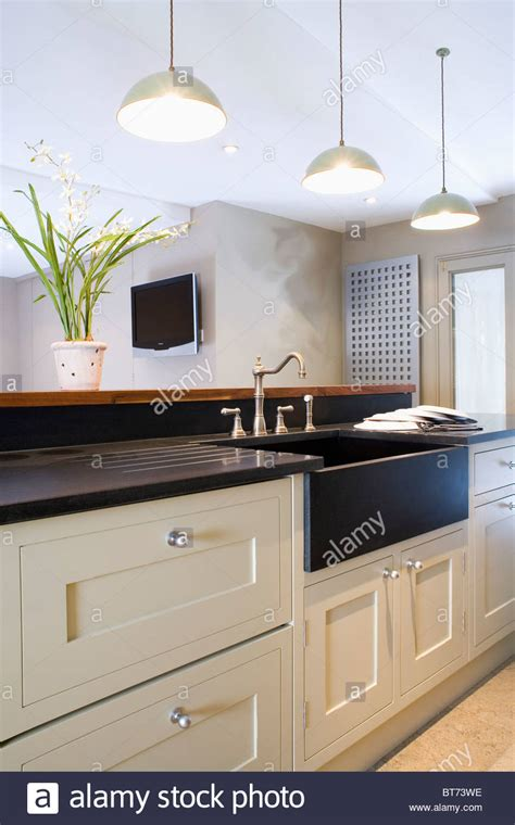black kitchen lights white pendant lights above black sink in fitted island unit stock photo royalty free