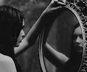 black woman looking in mirror study shows women who deem themselves unattractive are