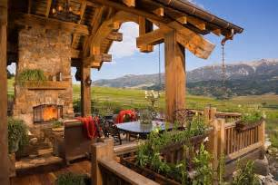 Stone fireplace and a cozy sitting area for the rustic deck design