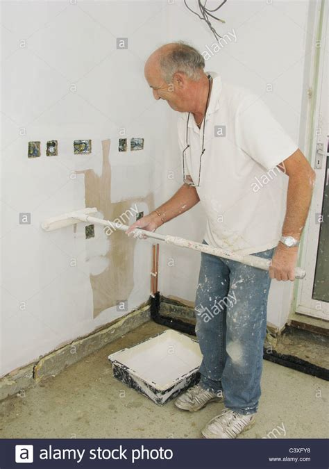 painter decorator painting newly plastered walls stock