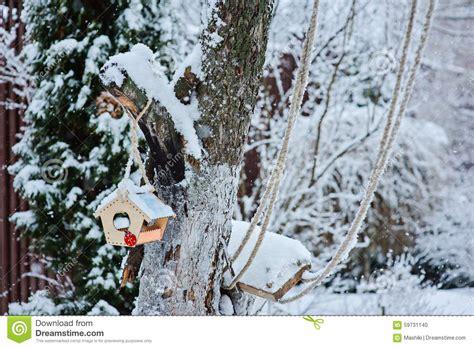 winter backyard wooden bird feeder on tree in snowy winter garden stock