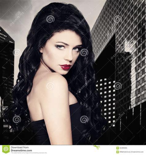 mujer con el pelo negro largo sano lujuriante foto de mujer morena de la moda con el pelo rizado negro largo