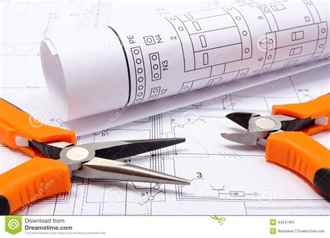 metal pliers and rolled electrical diagram on construction