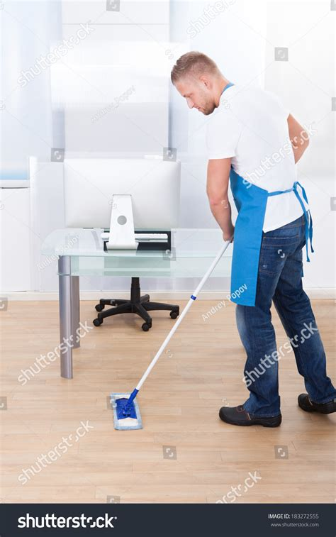 handsome janitor or cleaner cleaning the floor in an