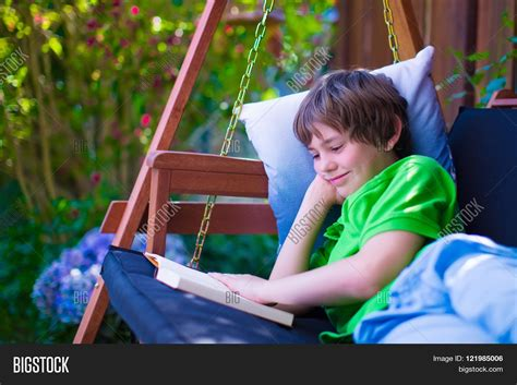 reading swing happy school boy reading a book in the backyard child