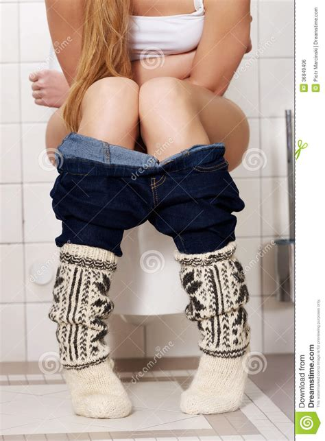 bathroom problems while pregnant young caucasian woman is sitting on the toilet urinary