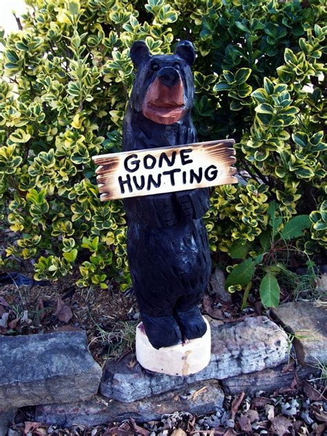 hand  chainsaw carved bears holding  signs