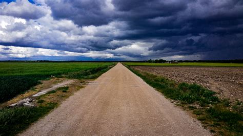 dirt road surrounded  green field  cloudy sky