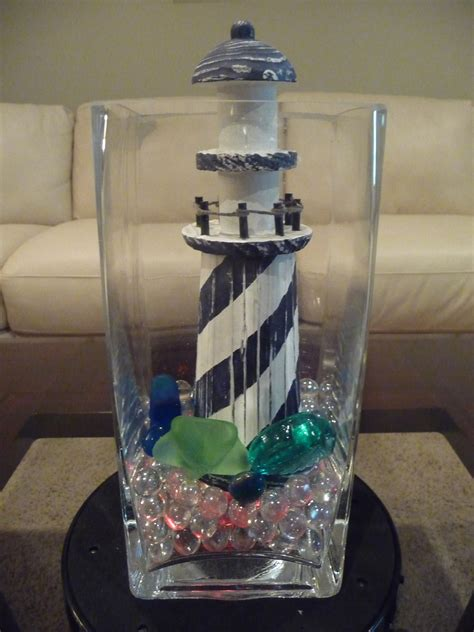 blue and white lighthouse fills this vase with sand