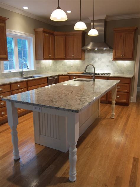 white kitchen island with granite countertop and prep sink