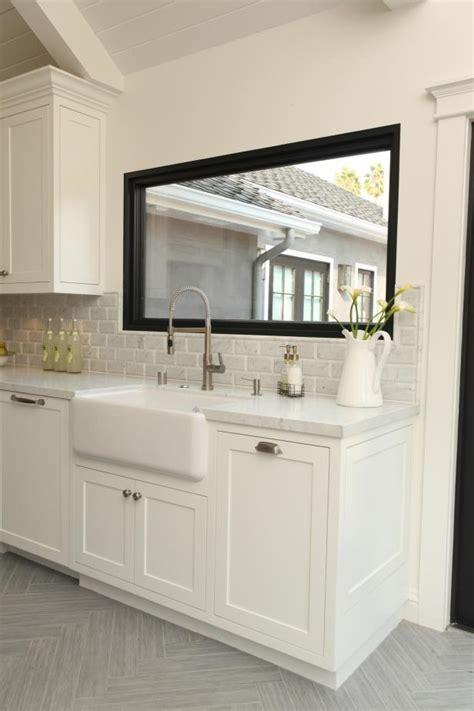 transitional white kitchen features black window frame