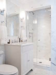 white cabinets an alcove shower a two piece toilet white tile and