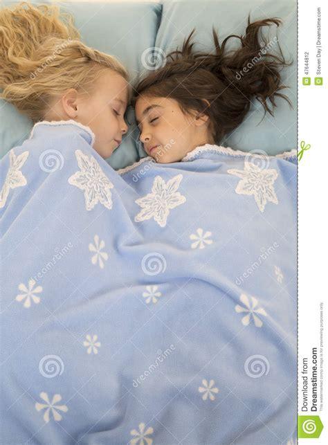 deux jeunes filles dans le lit endormi sous une couverture