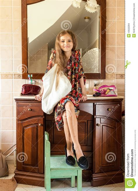 girls using bathroom girl in mothers clothes sitting on sink at bathroom stock