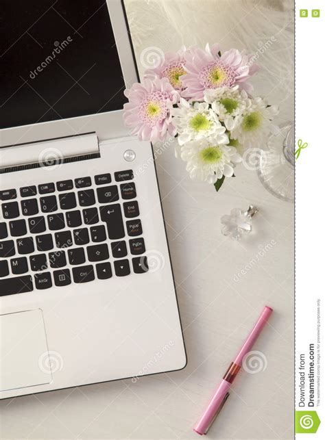 pink laptop desk laptop on desk with flowers stock photo image 73974430