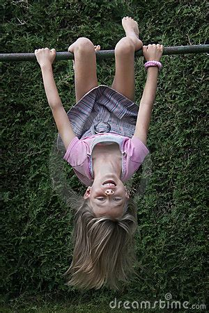 child hanging upside down on climbing frame stock