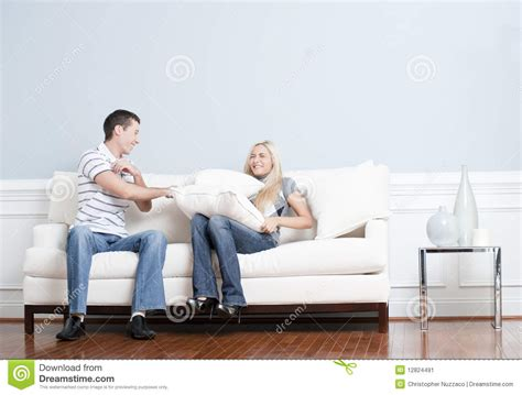 having on couch young couple having a pillow fight on sofa stock image