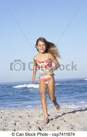stock photo of young girl running along sandy beach