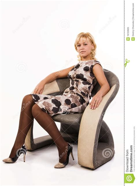 woman in an armchair beautiful woman sits in an armchair stock photo image