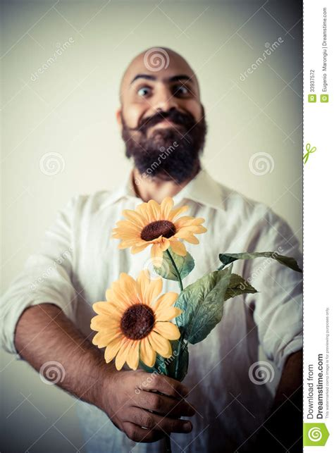 long beard  mustache man giving flowers stock photo
